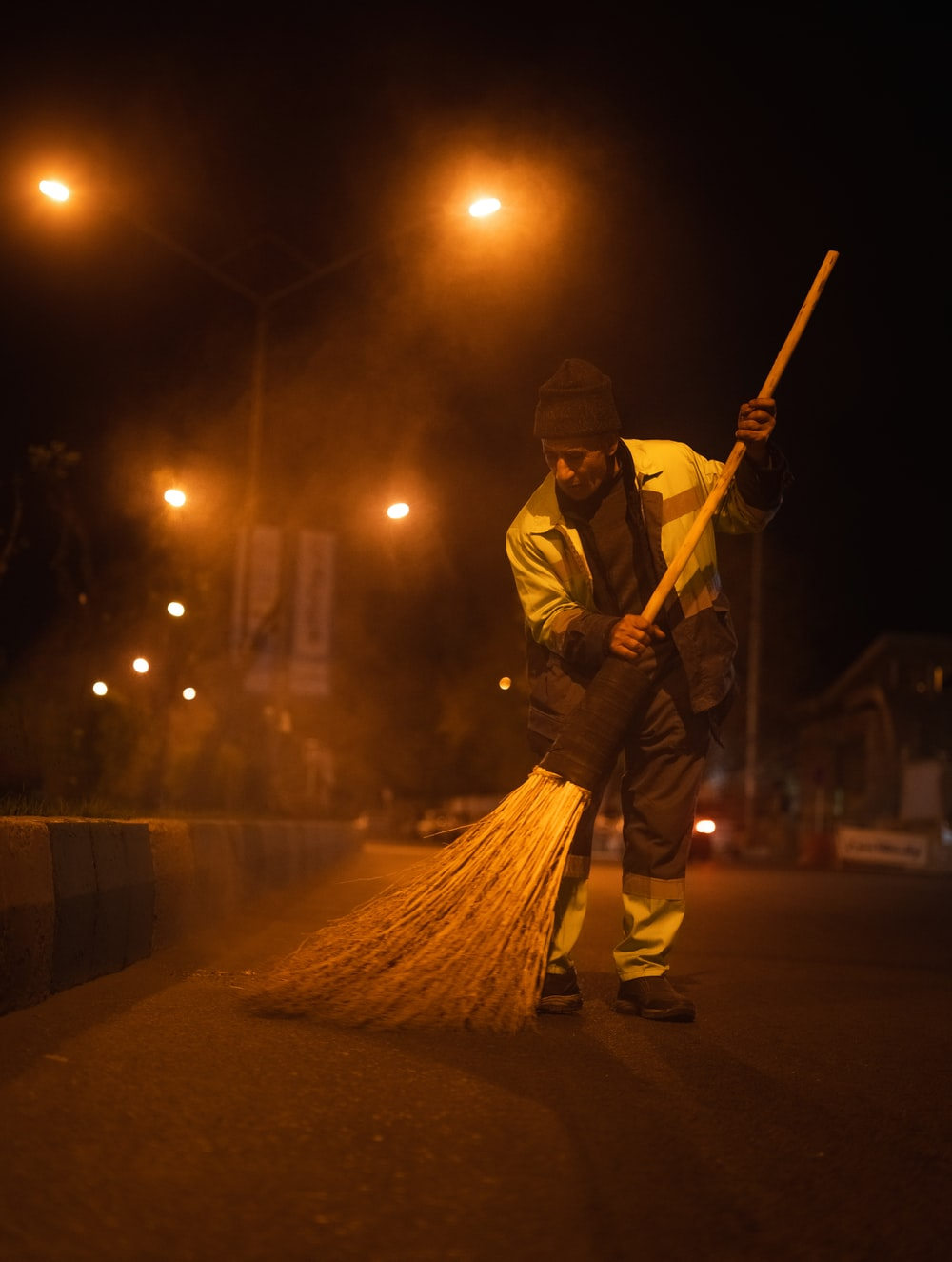 man in yellow jacket holding broom