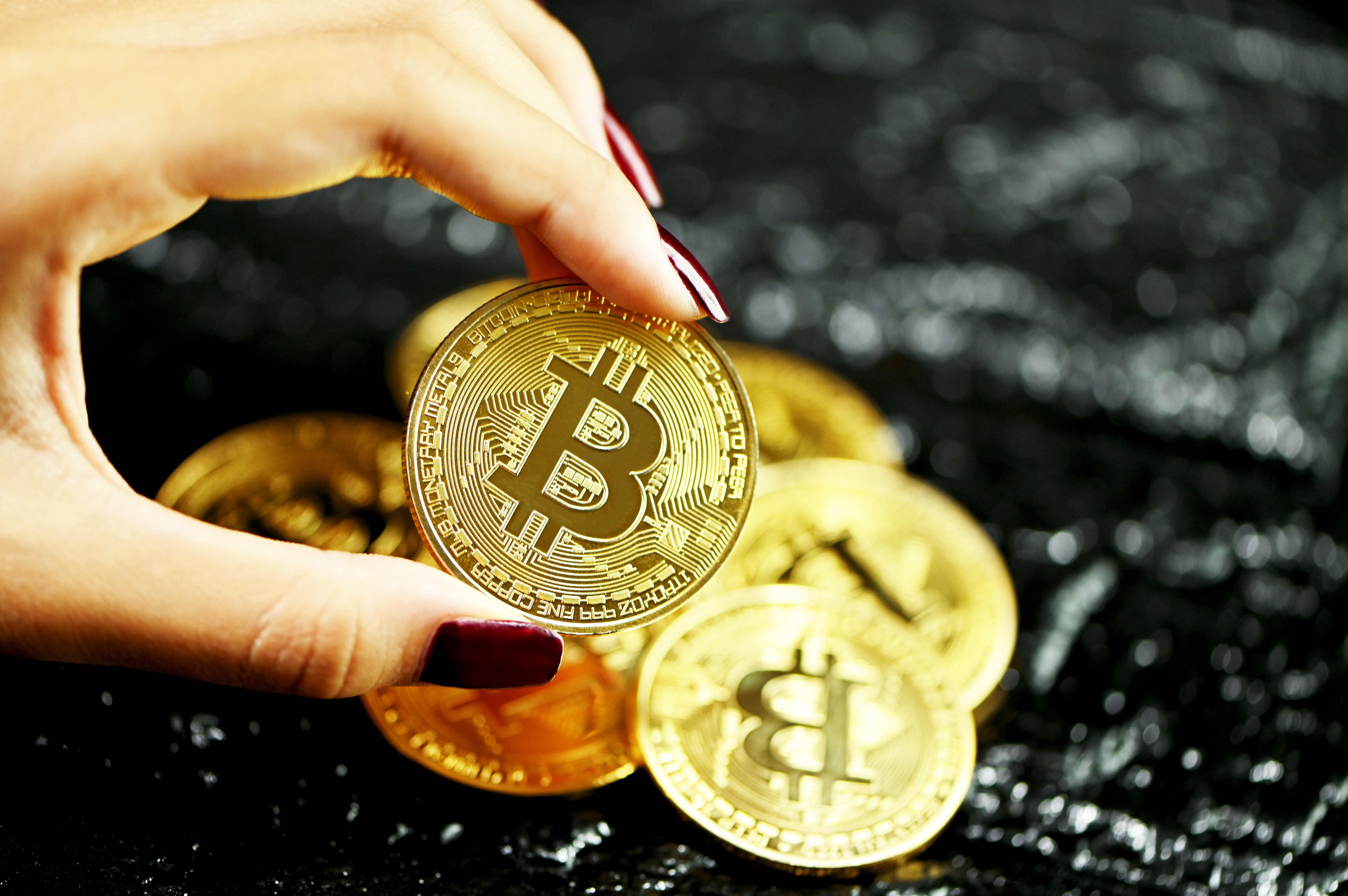 Bitcoin held in one hand with scarlet-colored nails against a pile of Bitcoins.