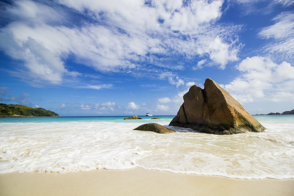 brown rock formation on sea shore under blue and white sunny cloudy sky during daytime