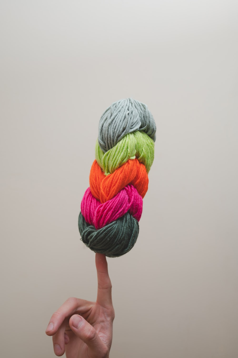 person holding green and purple yarn