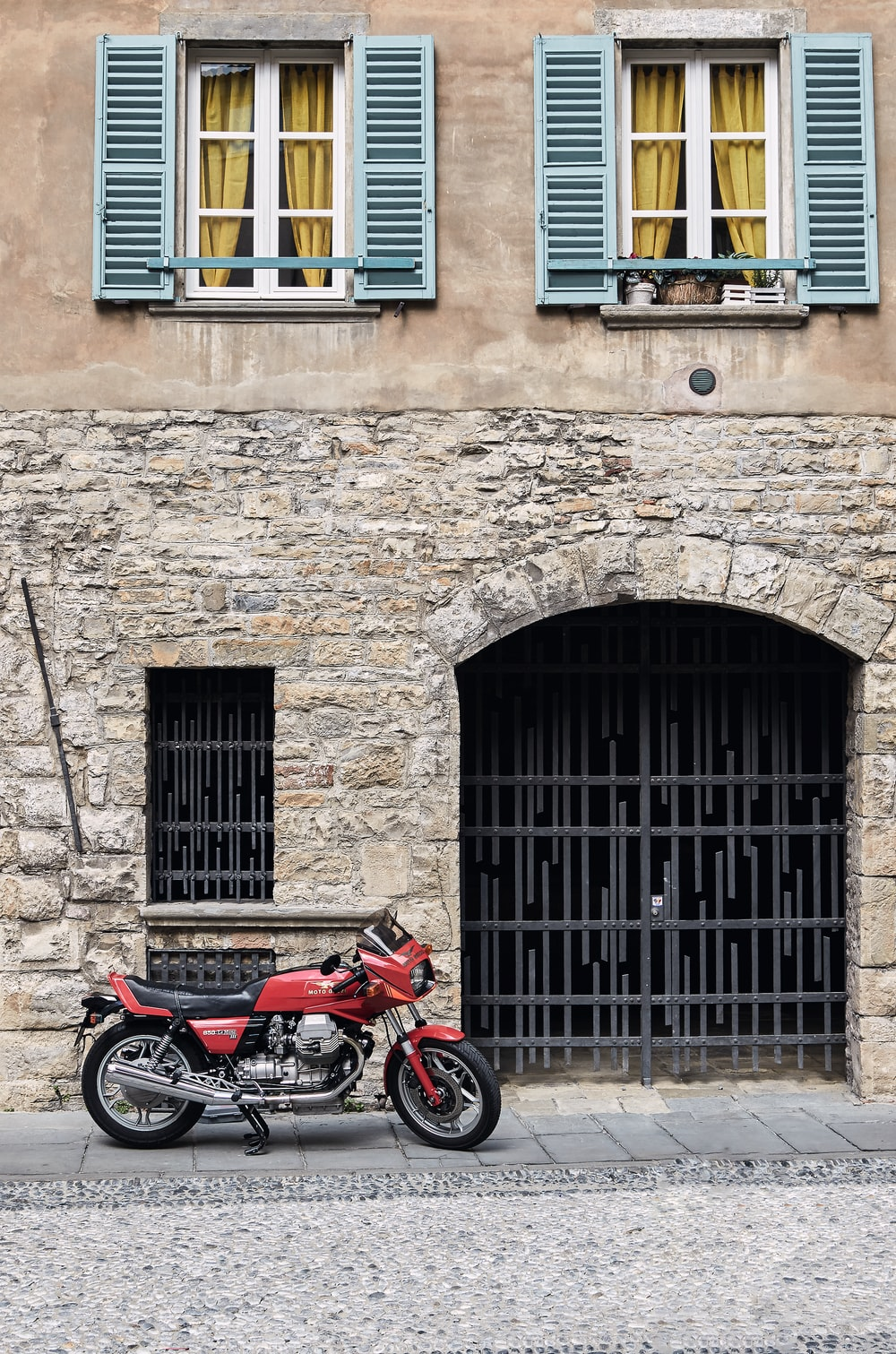 red and black motorcycle parked beside brown brick building