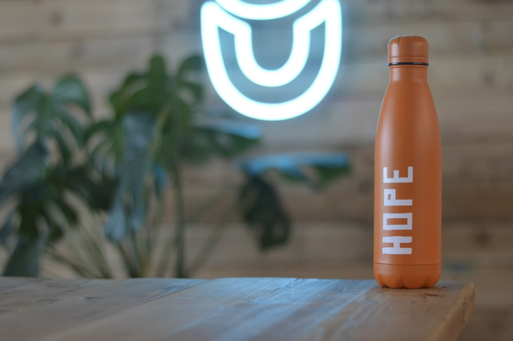 orange and white plastic bottle on brown wooden table