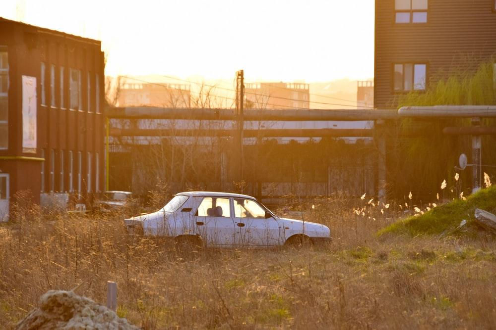 white sedan parked near brown building during daytime