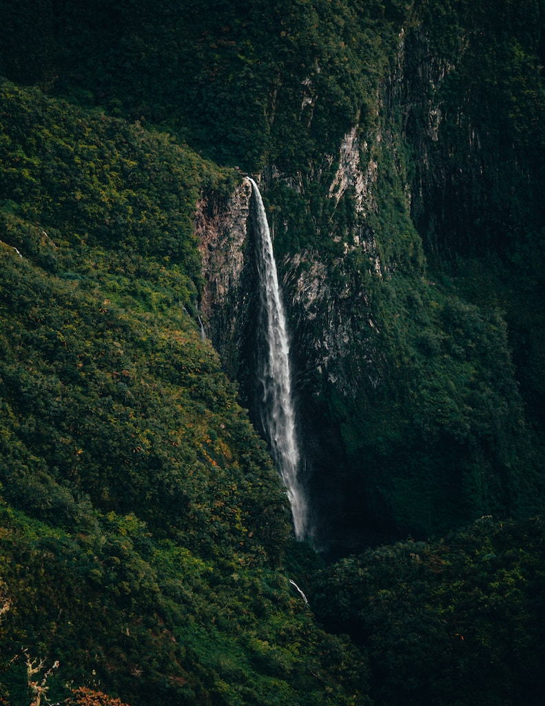waterfalls in the middle of green mountain
