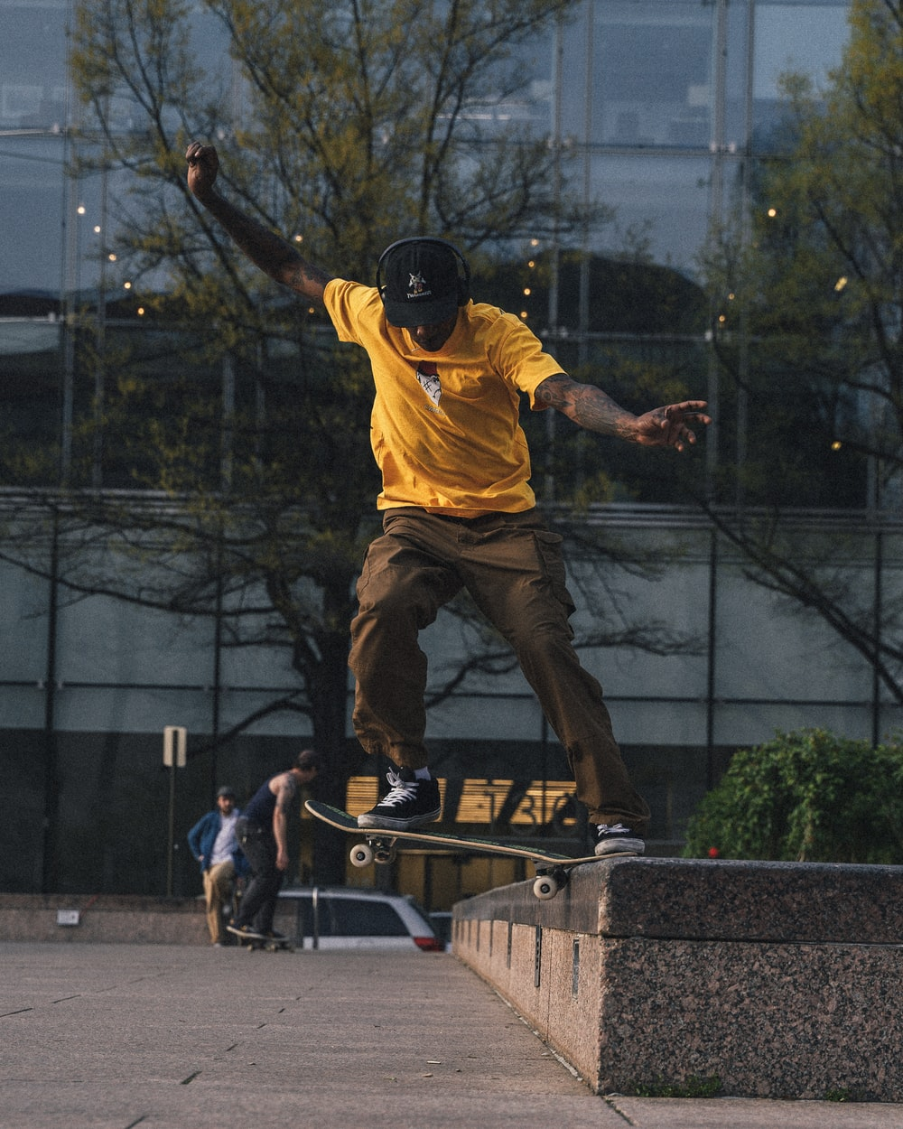man in yellow shirt and brown pants playing skateboard