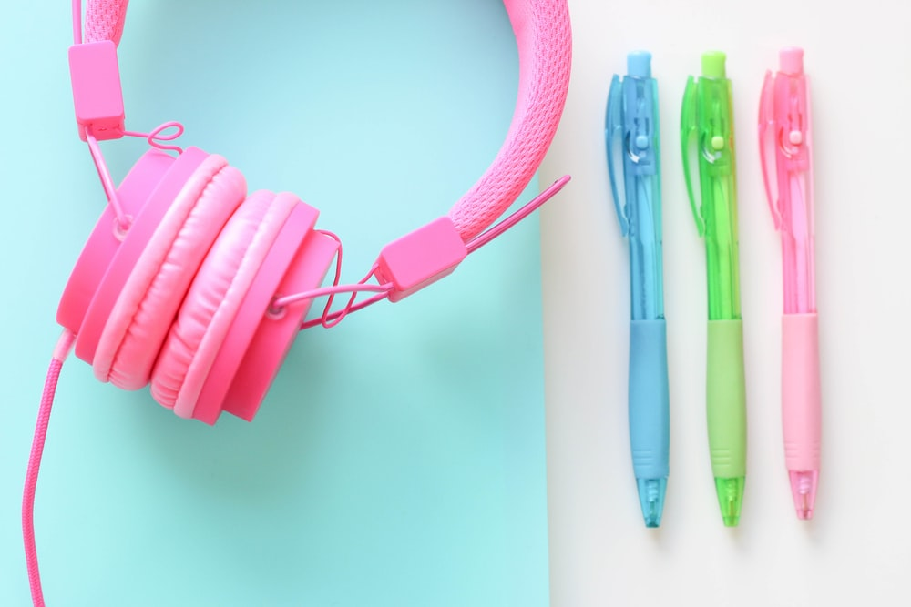 pink and blue click pen beside pink headphones
