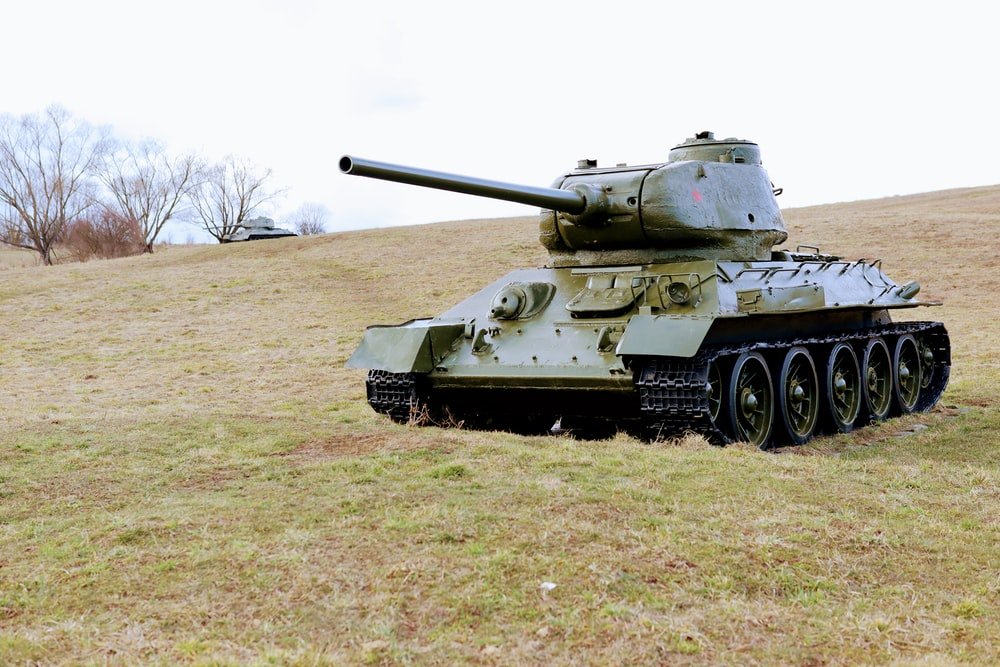 green battle tank on green grass field during daytime
