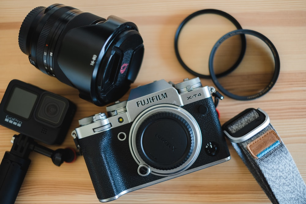 black and silver canon dslr camera on brown wooden table