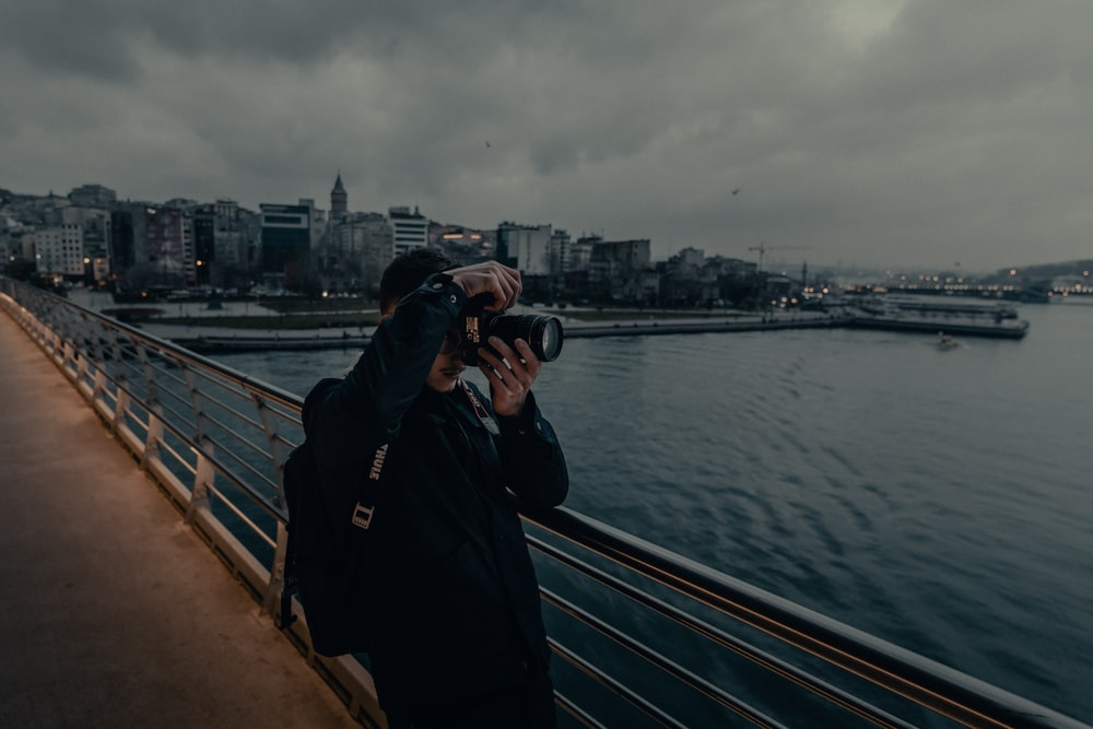 man in black jacket and black cap standing on bridge