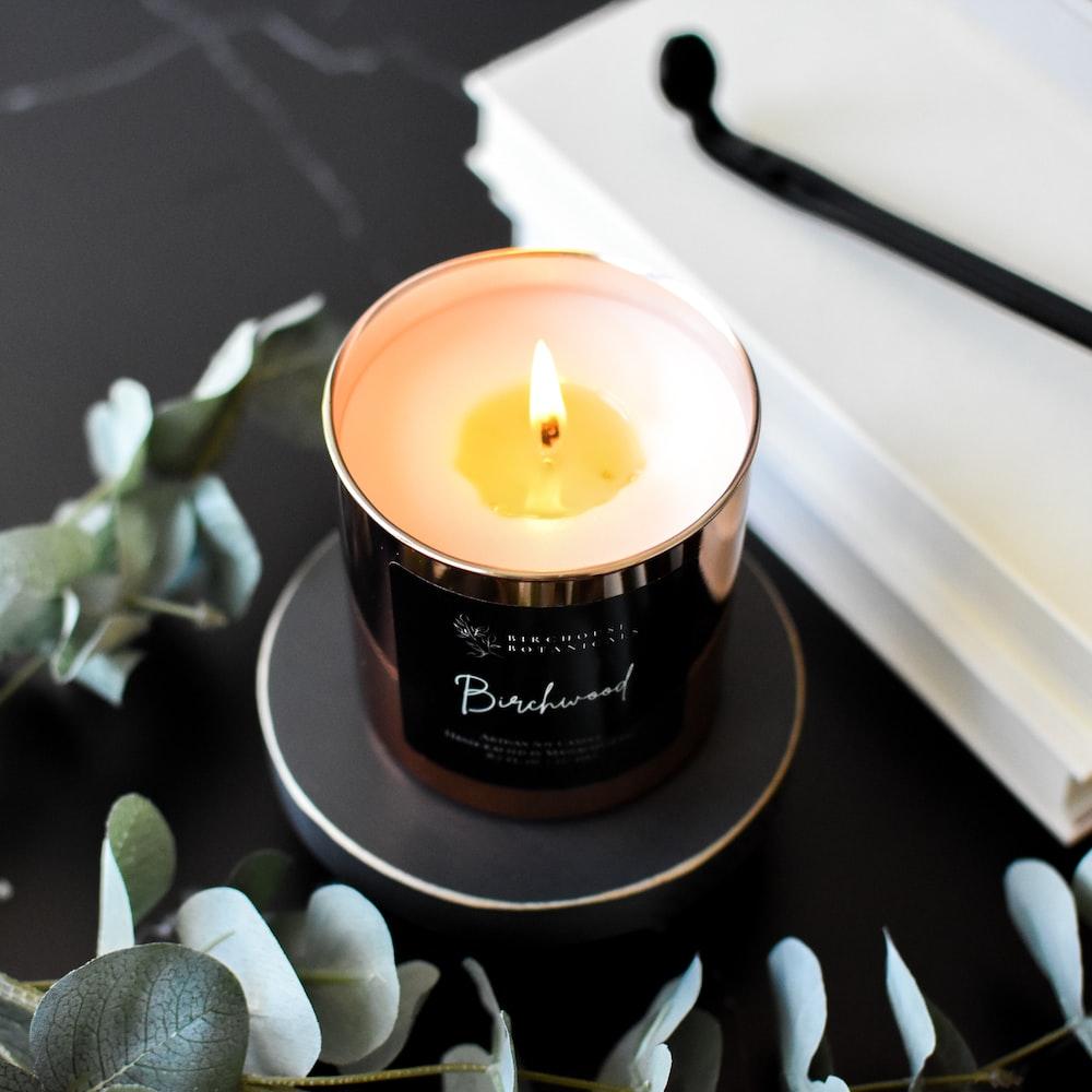 lighted candle on black ceramic saucer