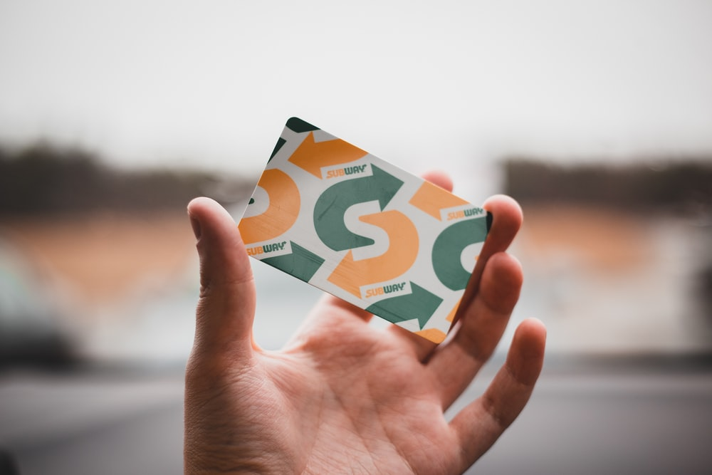 person holding green and white card