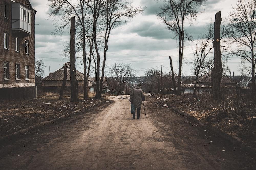 man in gray jacket walking on dirt road during daytime