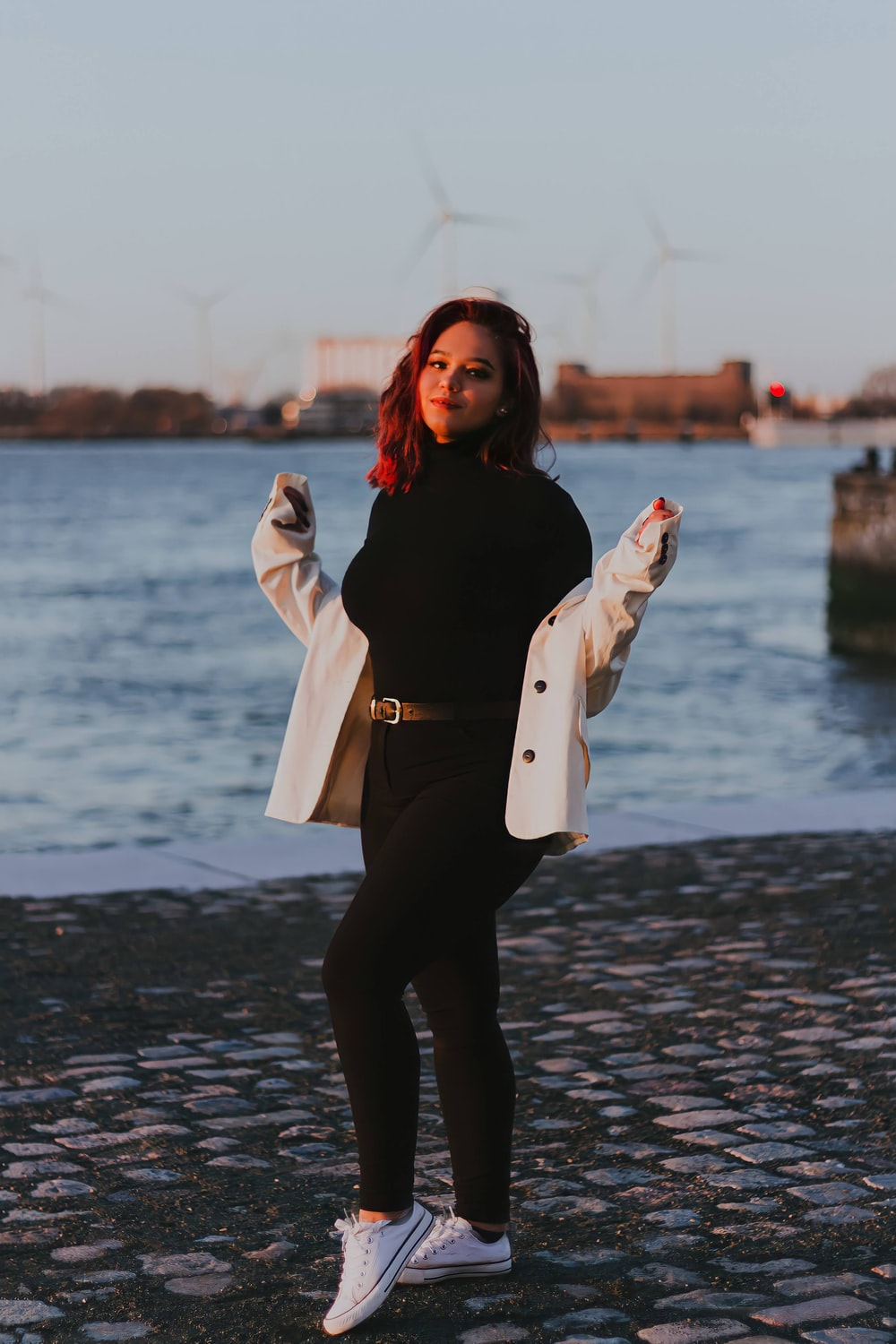 woman in black jacket and black pants standing on wet ground