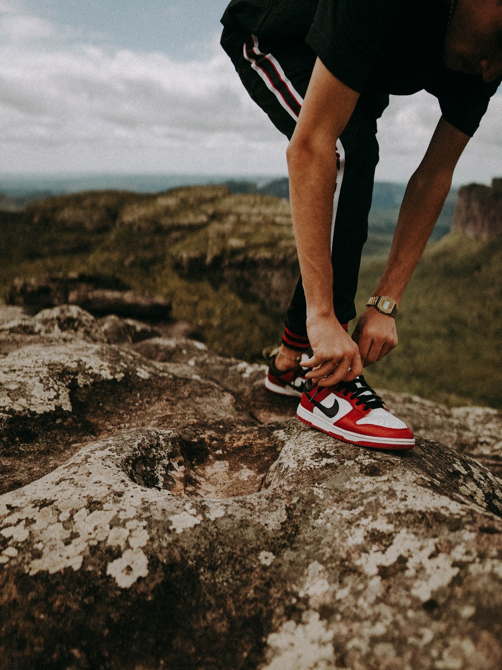 person in black shorts and red nike sneakers standing on rocky ground during daytime