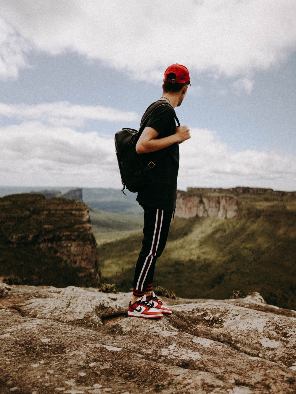 man in black t-shirt and black pants wearing red and white nike shoes standing on on on on on