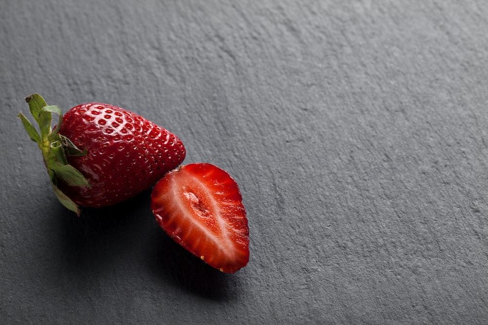 2 strawberries on white textile