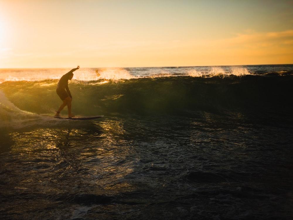 woman in black bikini walking on beach during daytime