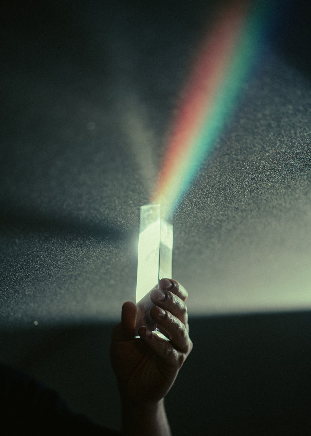 person holding white box with rainbow light