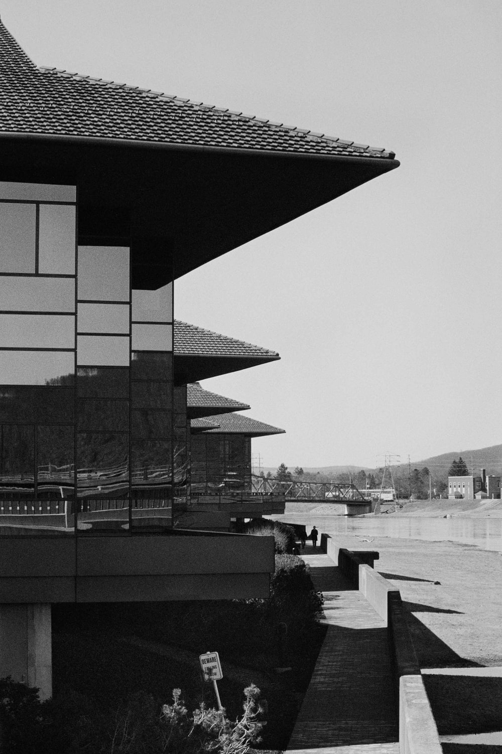 grayscale photo of building near body of water