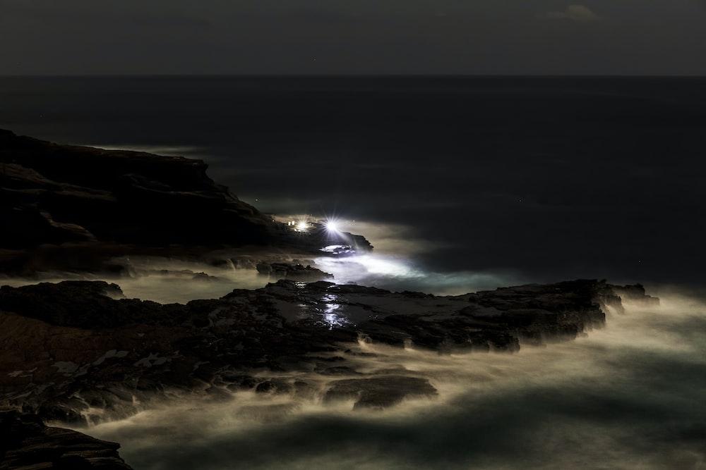 ocean waves crashing on shore during night time