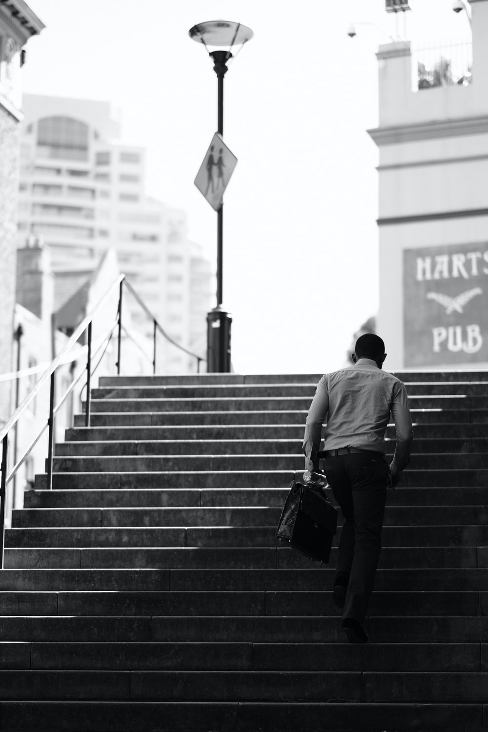 man in black t-shirt and black pants walking on stairs