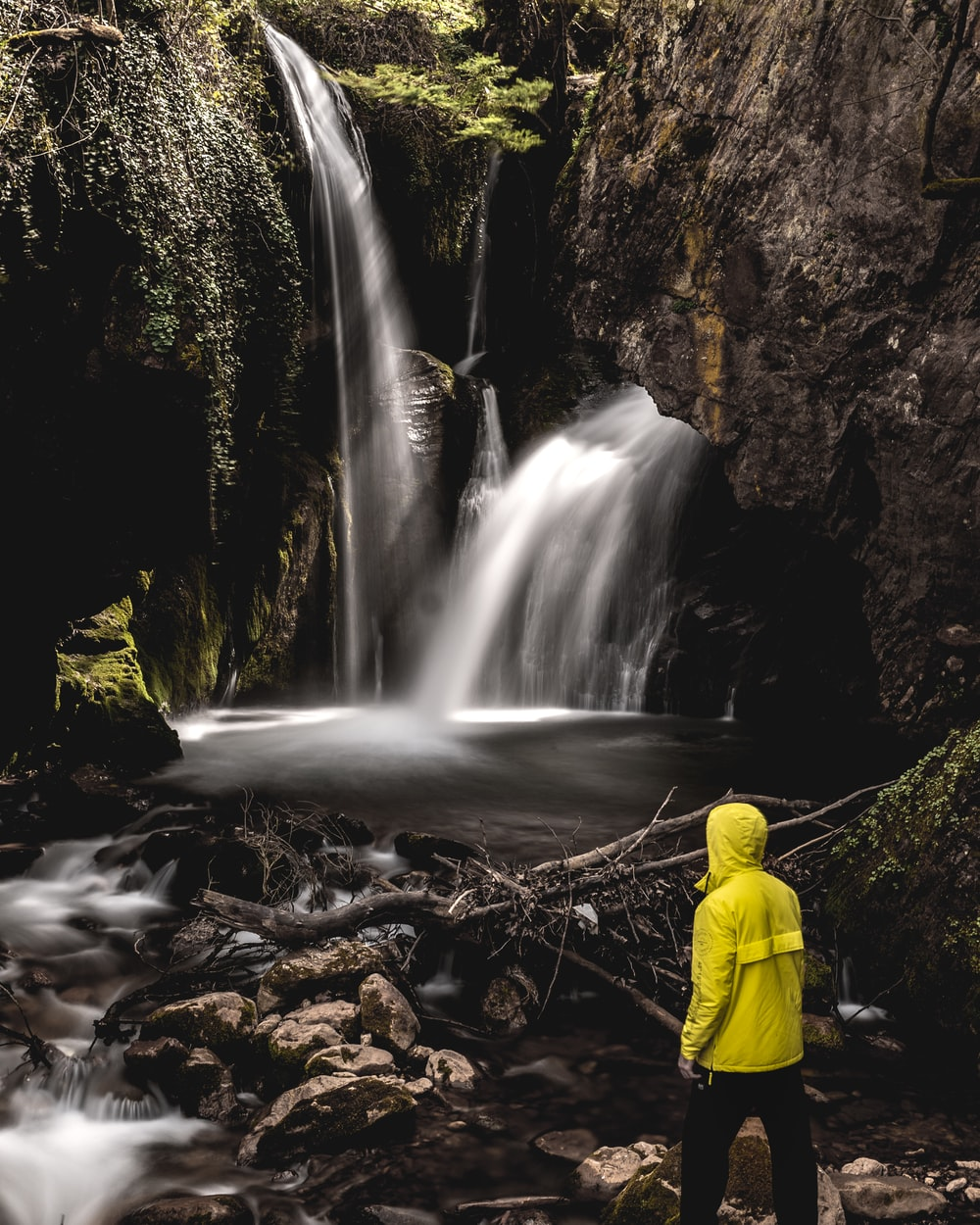 man in yellow jacket standing in front of waterfalls during daytime