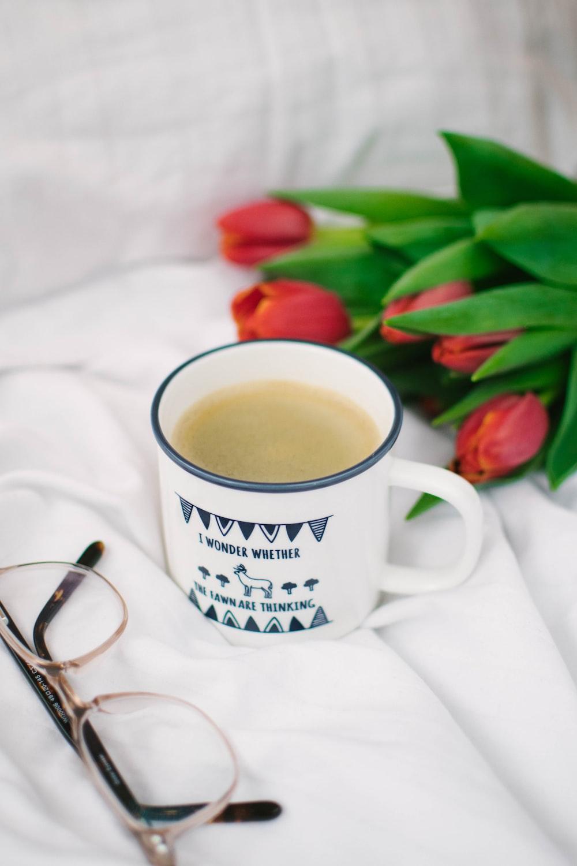 white ceramic mug with coffee on white textile
