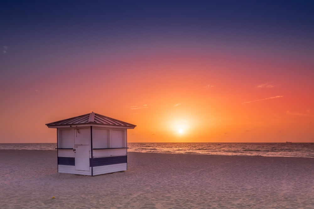 white wooden house on beach during sunset