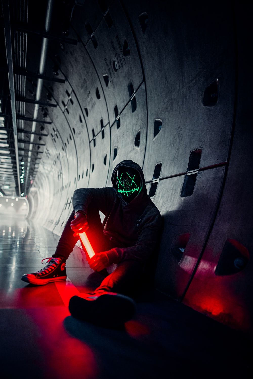 man in black and red suit wearing helmet sitting on tunnel