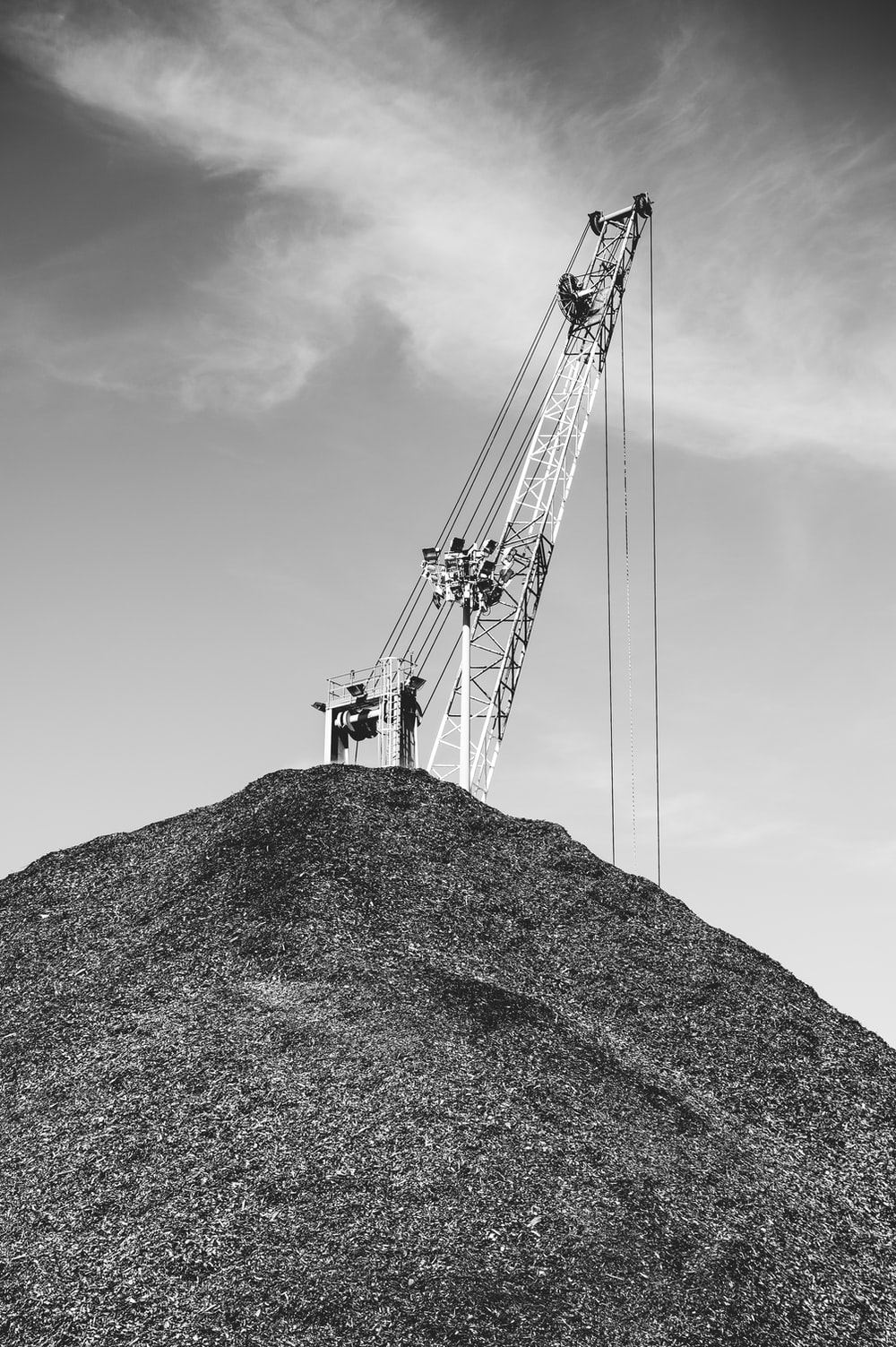 grayscale photo of crane on top of hill