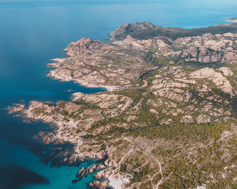 aerial view of green and brown mountains and blue sea during daytime