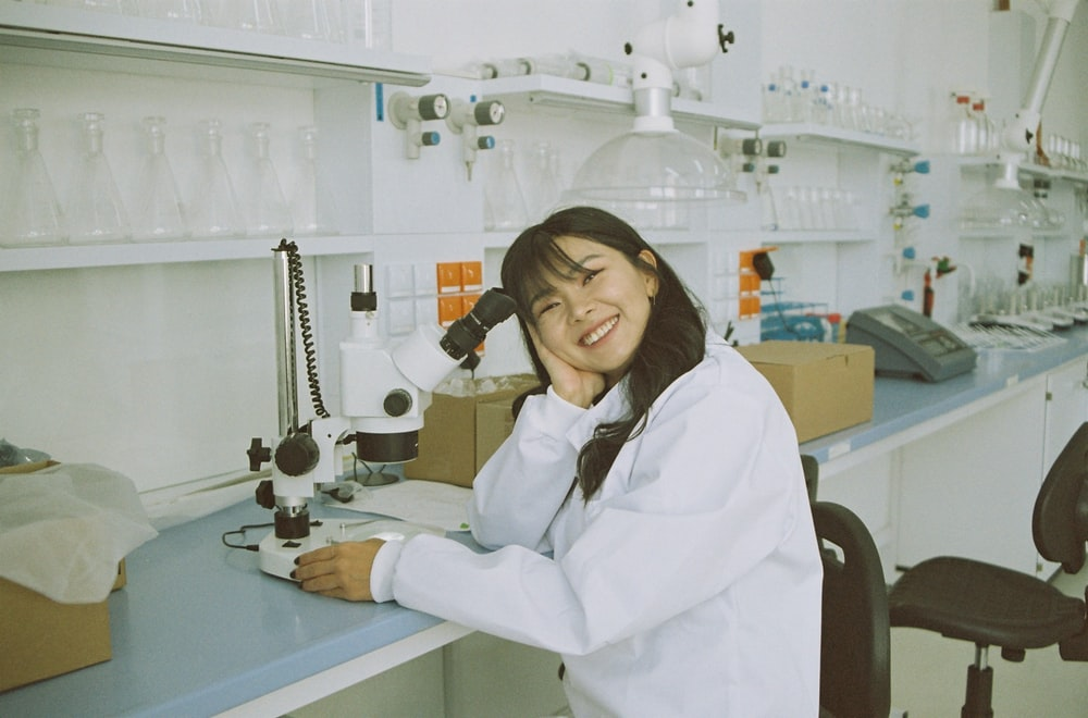 woman in white laboratory gown holding black microphone