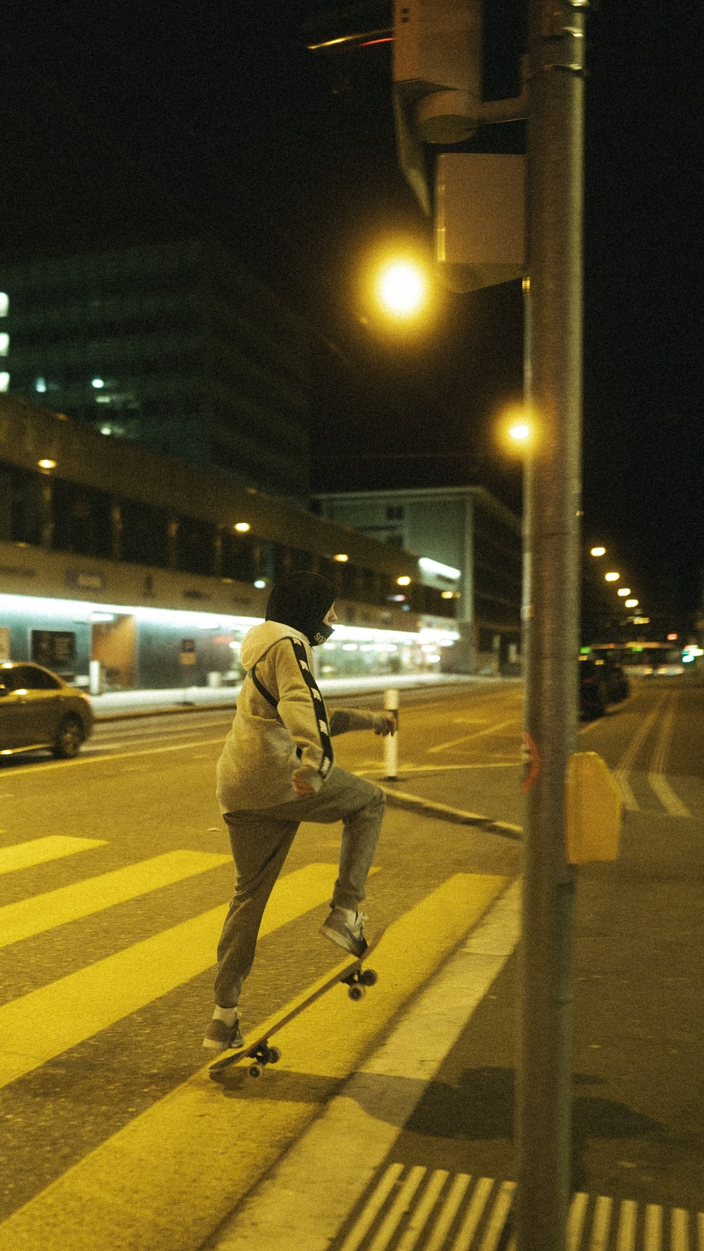 man in brown jacket and pants standing on sidewalk during night time