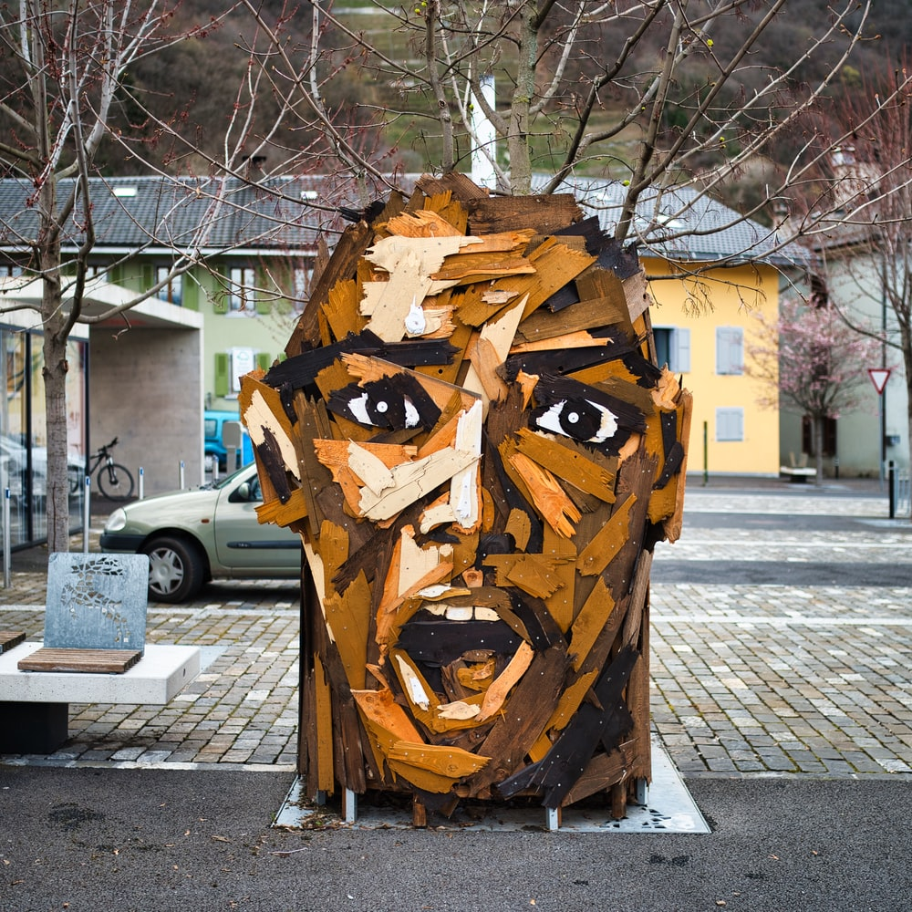 brown wooden human face carved statue on gray concrete road during daytime