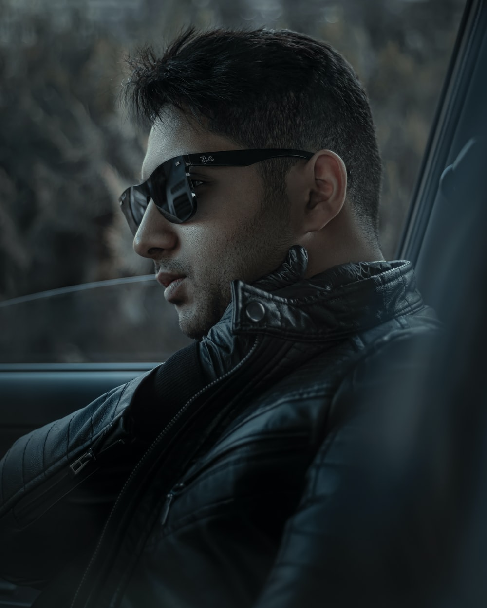 man in black leather jacket wearing black sunglasses