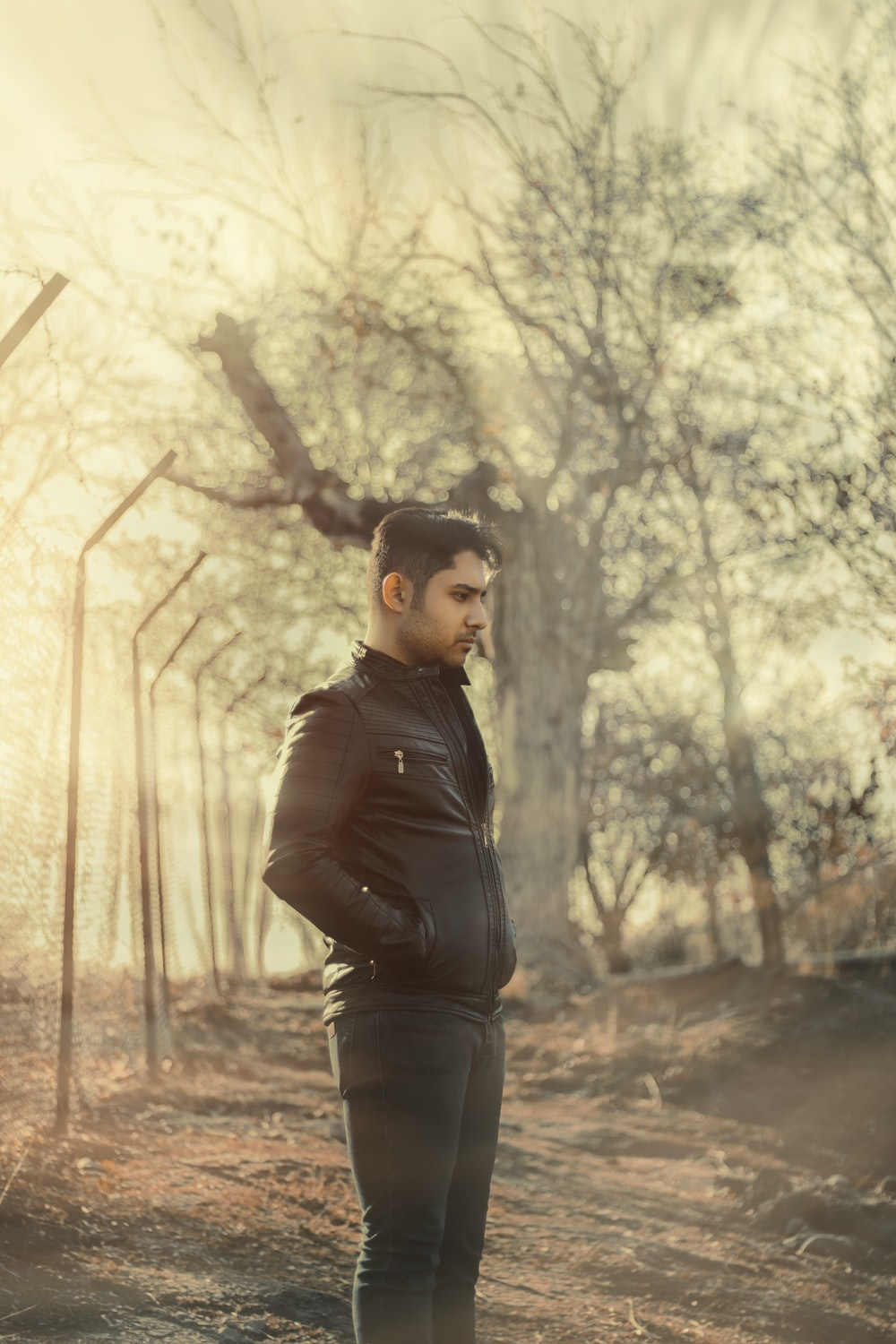 man in black leather jacket standing near trees during daytime