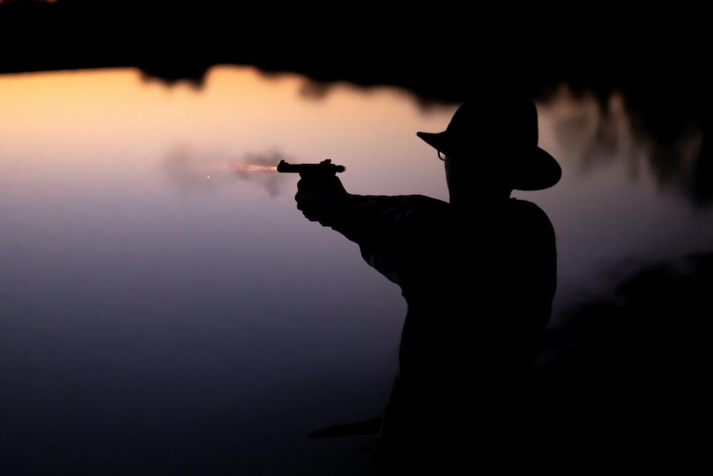 silhouette of man holding gun