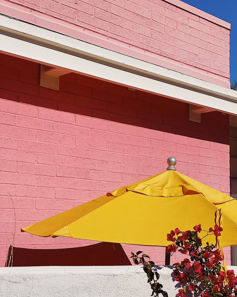 red and yellow umbrella near brown brick wall