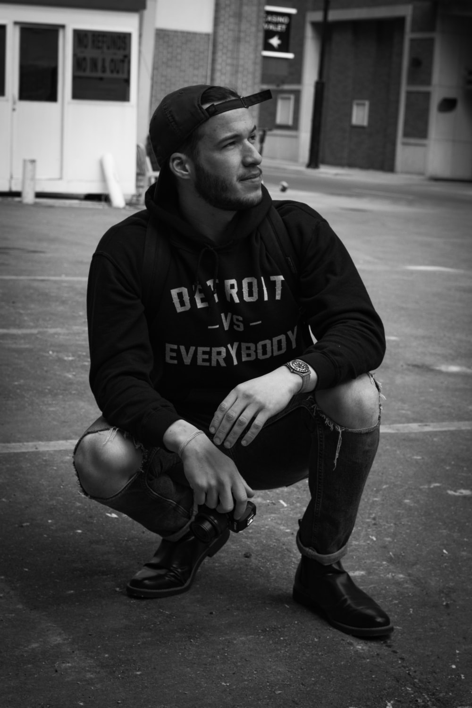 man in black hoodie and black pants sitting on the ground