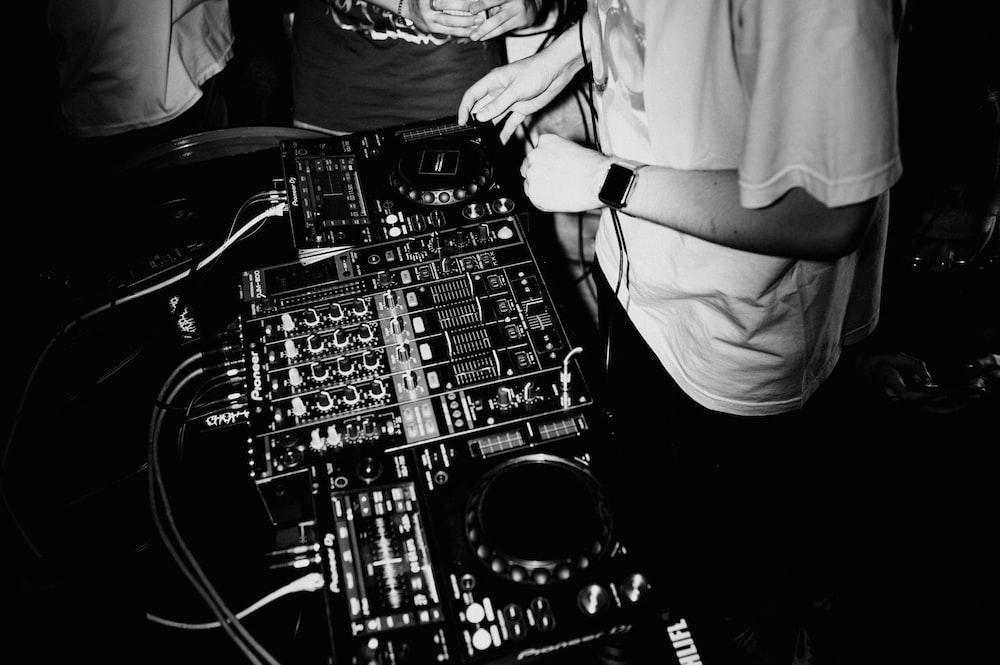 man in white dress shirt playing audio mixer