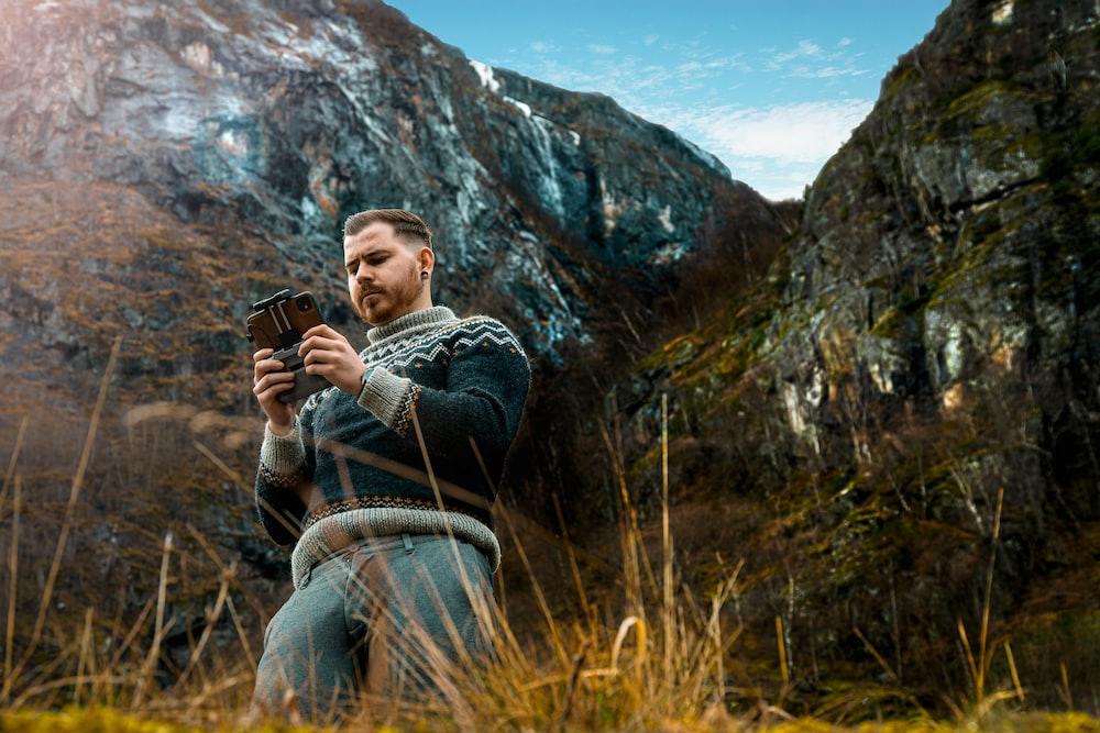 man in black jacket sitting on brown grass field during daytime