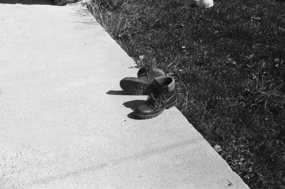 grayscale photo of person wearing black shoes