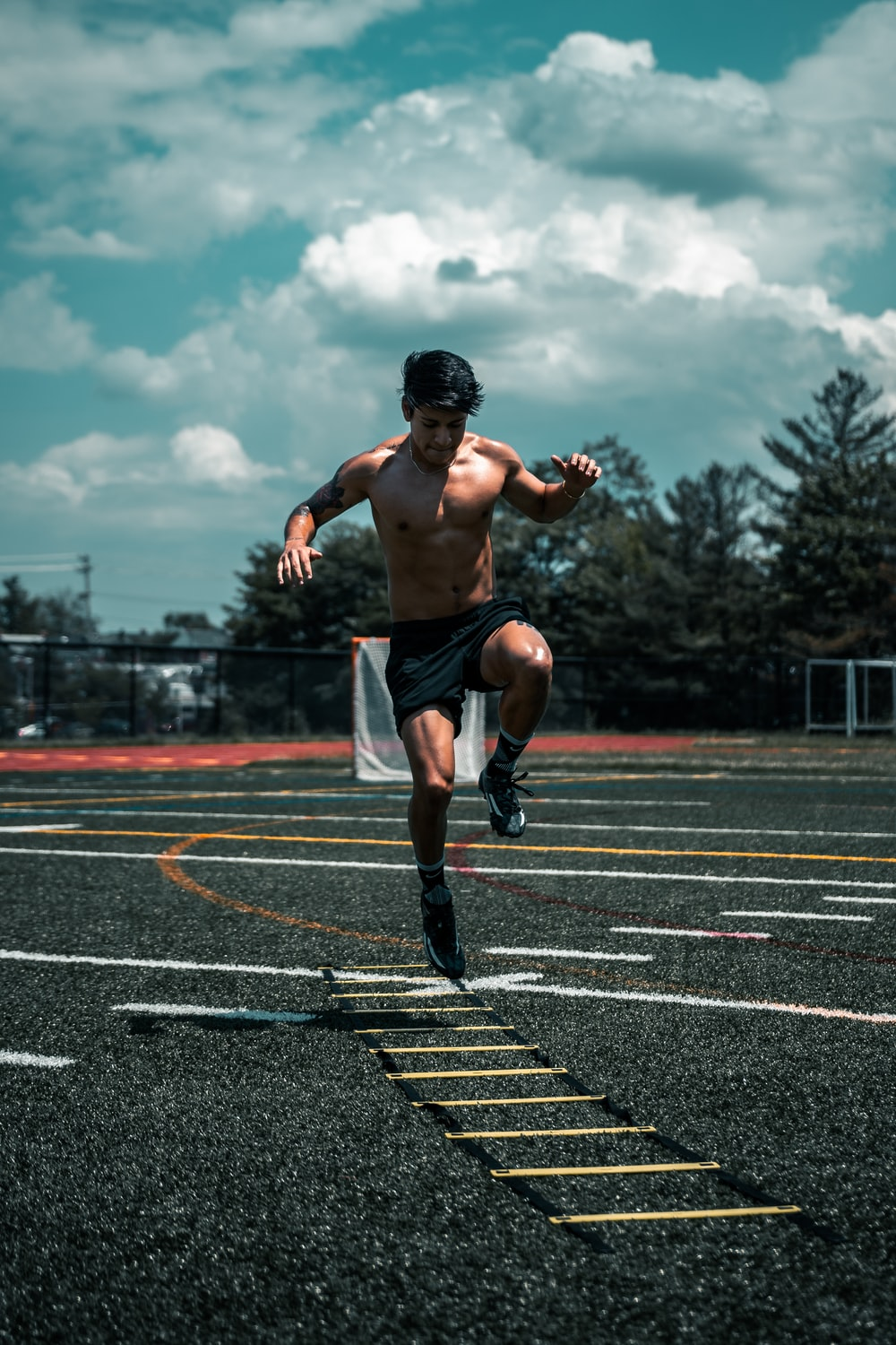 man in black shorts running on track field during daytime
