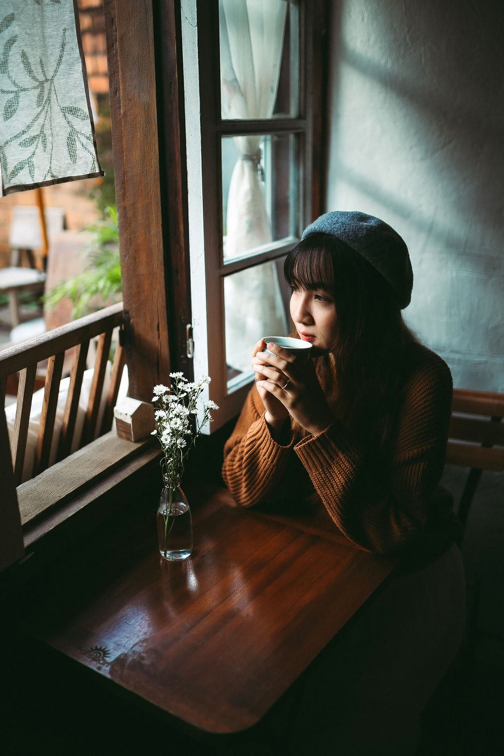 woman in black knit cap sitting on brown wooden chair