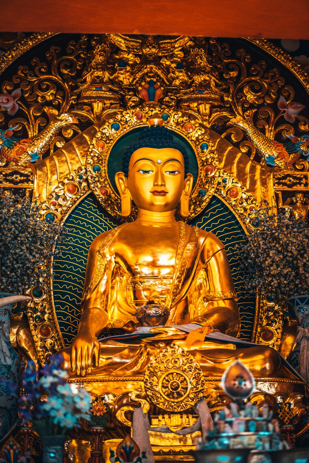 gold buddha statue on gold and blue floral wall