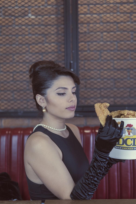 woman in black tank top holding burger