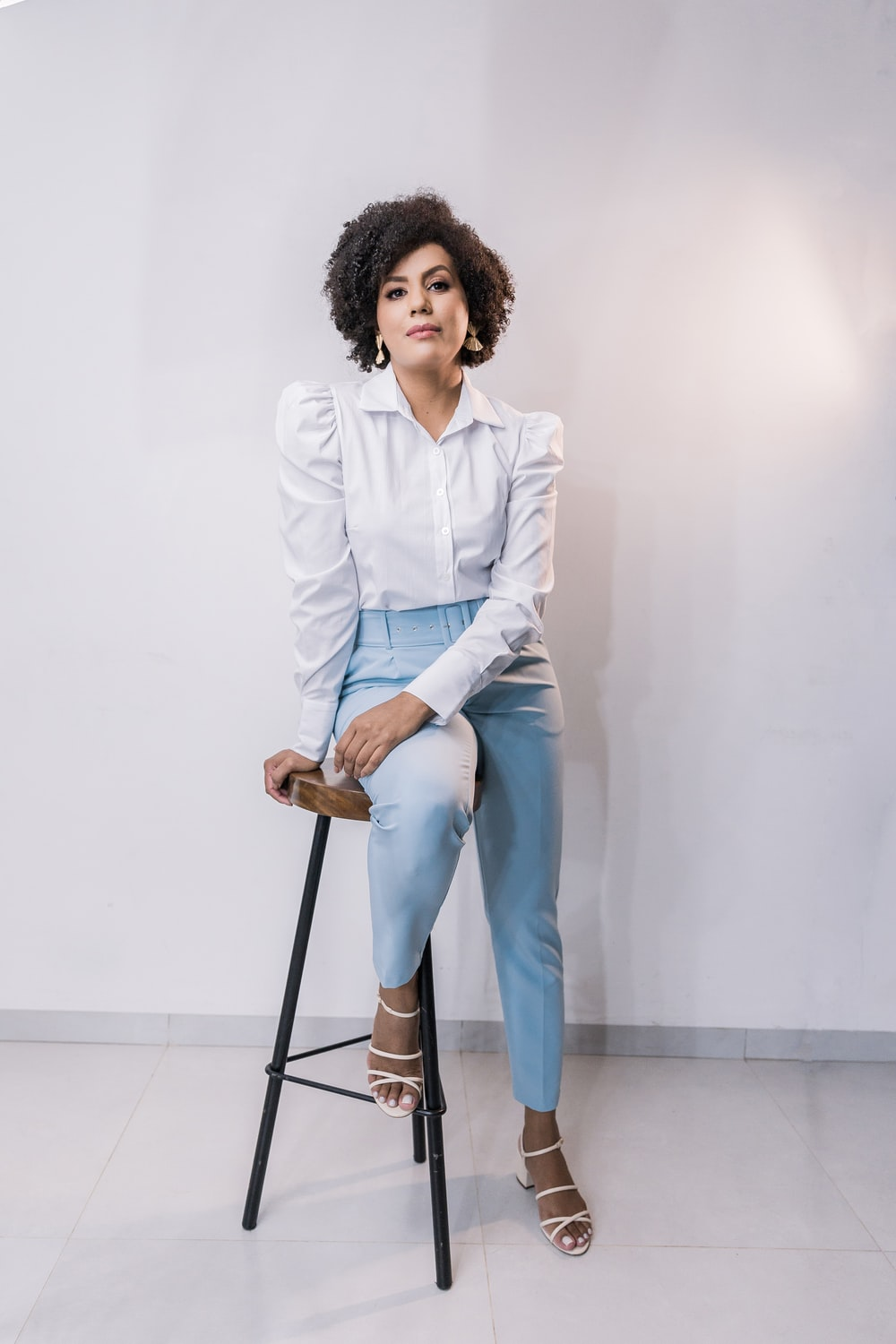 woman in white dress shirt and blue denim jeans
