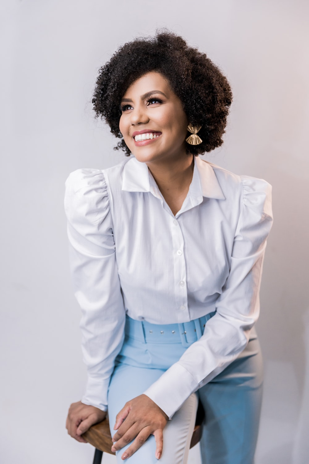 woman in white dress shirt and blue denim jeans smiling