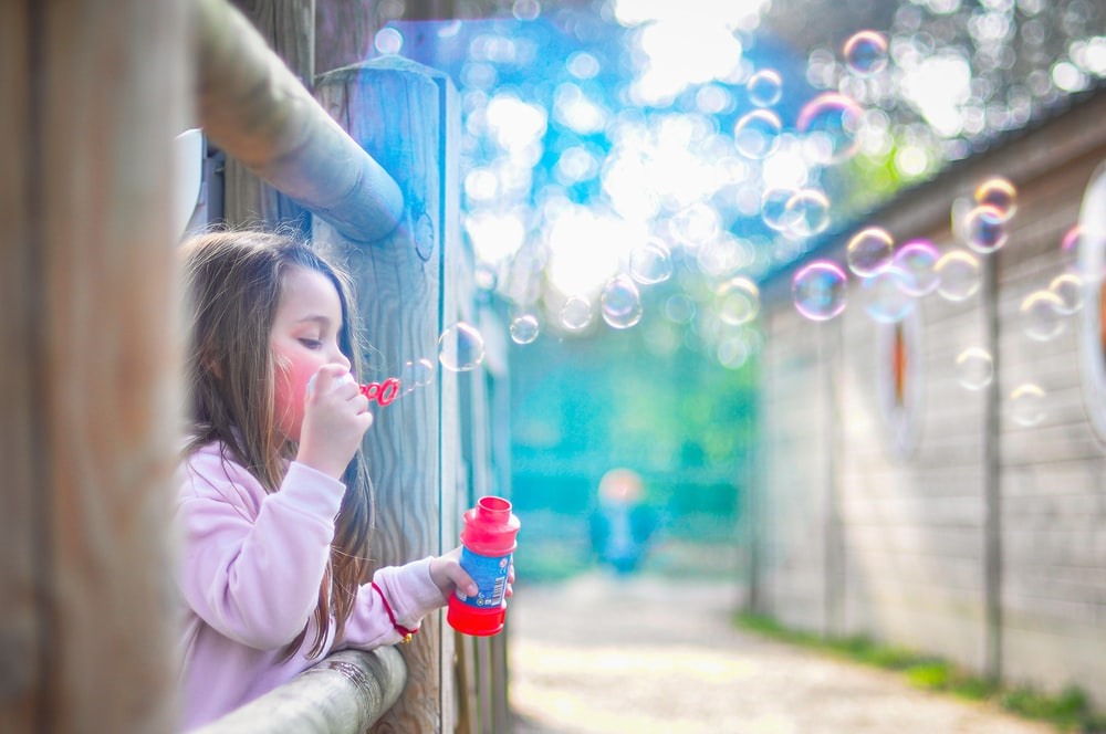 girl in pink jacket blowing bubbles during daytime