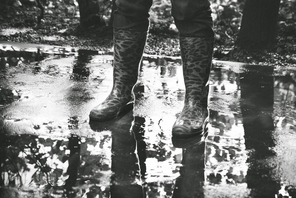 person in black pants and boots standing on water